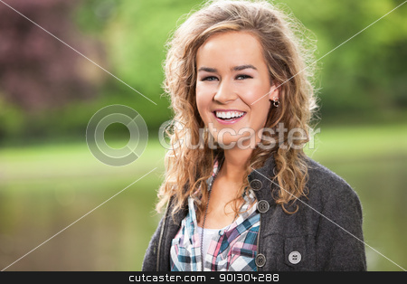Young female smiling outdoors stock photo, Beautiful young woman smiling outdoors in park by Tyler Olson