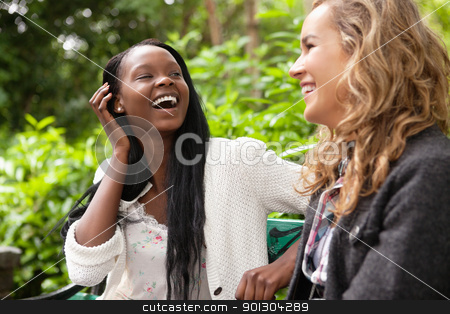 Cheerful women enjoying chat in the park stock photo, Close-up of two young female friends gossiping in park by Tyler Olson