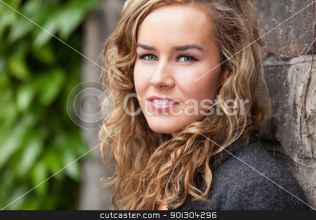 Young female leaning against wall stock photo, Portrait of beautiful young female leaning against stone wall by Tyler Olson