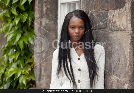 African American standing in front of stone wall stock photo, Portrait of African American female standing against stone wall by Tyler Olson
