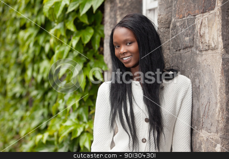 African American women in front of stone wall stock photo, Smiling African American female standing in front of stone wall by Tyler Olson
