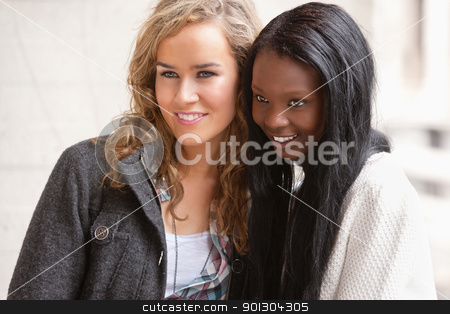 Female friends looking at something stock photo, Two female friends looking at something interesting by Tyler Olson