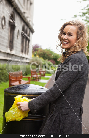 Woman putting plastic waste in garbage bin stock photo, Side view of happy young woman putting plastic waste in garbage bin by street by Tyler Olson