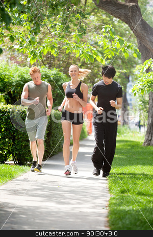 Friends jogging together in a park stock photo, Three friends jogging in the park against blur background by Tyler Olson