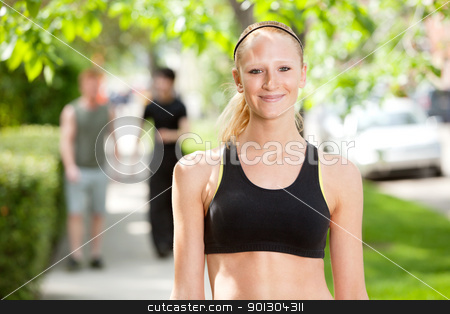 Close-up of a woman in park stock photo, Close-up of a beautiful woman in sports wear with friends in the background by Tyler Olson