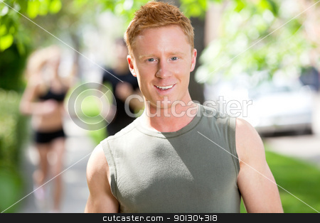Portrait of young man smiling stock photo, Portrait of a Caucasian man, people running in background by Tyler Olson