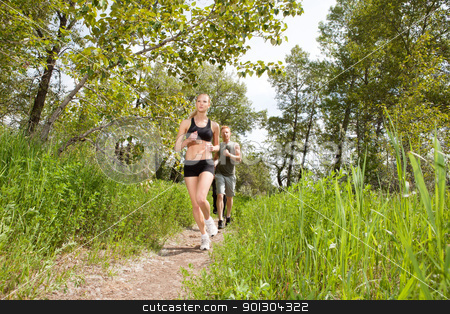 People in sportswear jogging stock photo, Young friends jogging together outdoors on a trail by Tyler Olson