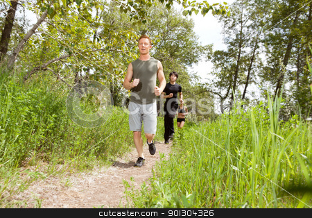 Friends exercising in forest track stock photo, Young friends jogging in the forest  on trail by Tyler Olson