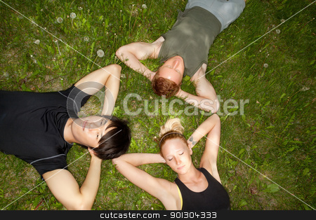 Friends lying down and resting stock photo, Close-up of friends resting on grass outdoors by Tyler Olson