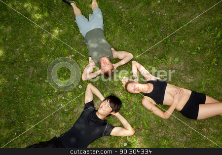 Friends lying and resting on ground stock photo, Closeup portrait of happy group of friends lying in circle by Tyler Olson
