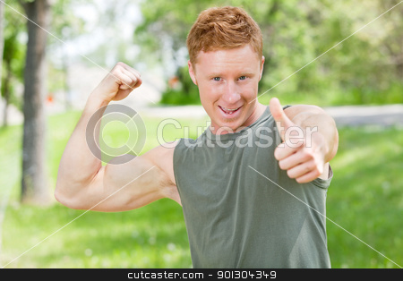 Man flexing and showing thumbs-up sign stock photo, Handsome man showing thumbs up sign while flexing by Tyler Olson