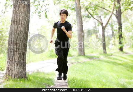 Portrait of man running in a park stock photo, Portrait of handsome man running against blur background by Tyler Olson