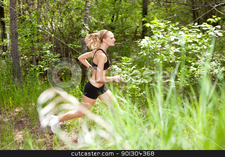 Woman running in the forest stock photo, Young woman running in the forest on trail by Tyler Olson