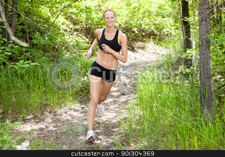 Woman smiling and running in forest stock photo, Portrait of beautiful young woman running in the forest by Tyler Olson