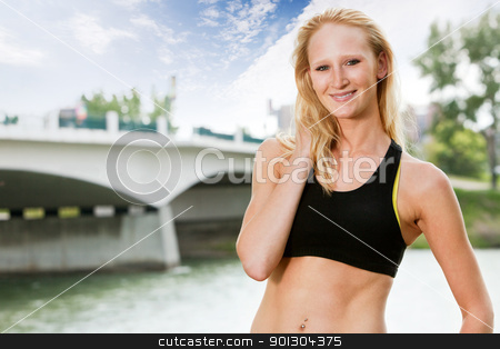 Portrait of woman in sportswear stock photo, Portrait of beautiful woman smiling near bridge by Tyler Olson