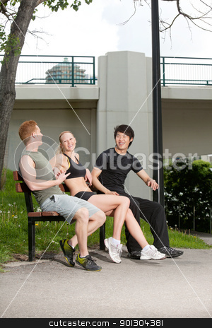 Happy friends laughing stock photo, Happy friends sitting in park and laughing against beach in the background by Tyler Olson