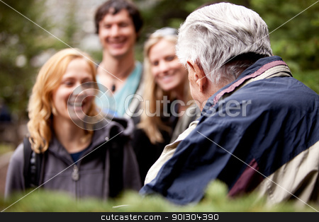 Elderly Hiking Guide stock photo, An elderly man talking to a group of young people in the forest. by Tyler Olson