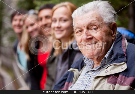 Elderly Man stock photo, An elderly man in front of a group of young people by Tyler Olson