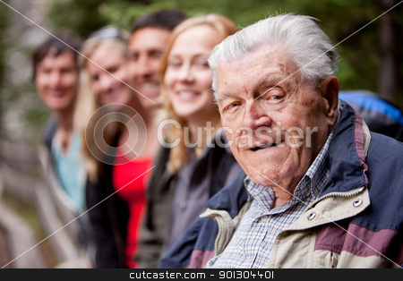 Grandfather Portrait stock photo, A portrait of a grandfather type man with a group of young people by Tyler Olson
