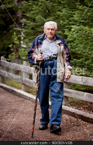 Elderly man Walking stock photo, An elderly man walking on a path through the forest by Tyler Olson