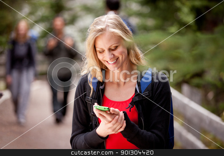 Woman Text Phone stock photo, A young woman reading a friendly text while outdoors by Tyler Olson