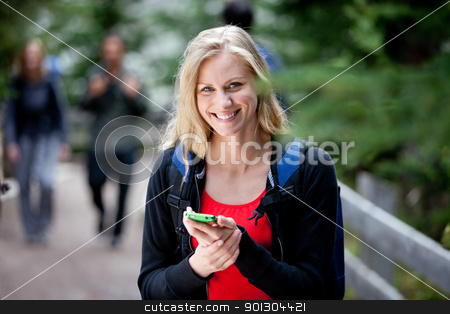 Happy Woman with Cell Phone stock photo, A happy woman holding a smart phone, looking at the camera by Tyler Olson