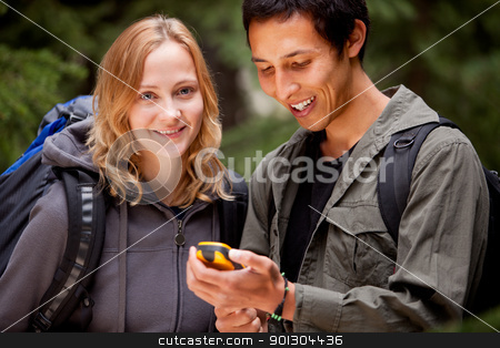 GPS Camping Friends stock photo, A man and woman looking at a gps in the forest by Tyler Olson