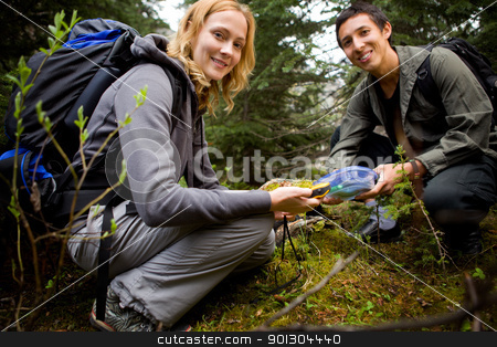 Finding a Geocache stock photo, Two people finding a geocache in the forest.  Shallow depth of field with sharp focus on woman. by Tyler Olson