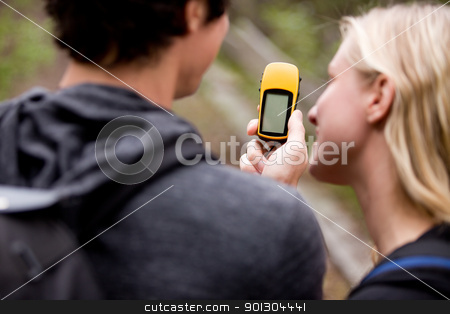 GPS stock photo, A couple outdoors in the forest using a GPS.  Sharp focus on the GPS device. by Tyler Olson
