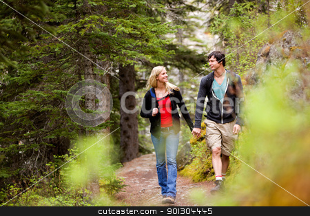 Walk Forest Couple stock photo, A happy couple looking at eachother and walking in the forest holding hands by Tyler Olson