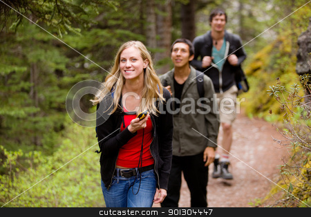 Woman with GPS in Forest stock photo, A woman using a GPS in the forest on a camping hike by Tyler Olson