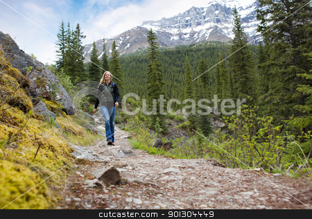 Happy Woman on Mountain Hike stock photo, A happy woman walking on a path on a mountain hike in Banff National Park by Tyler Olson