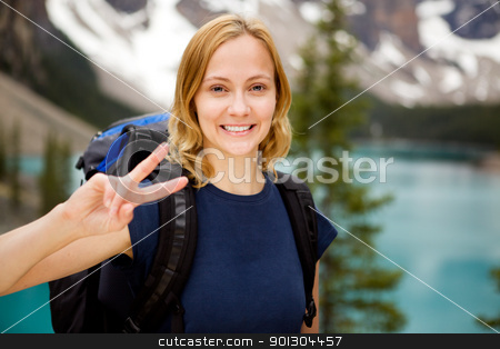 Portrait at Mountain Lake stock photo, A portrait of a happy smiling girl with a mountain lake in the distant background by Tyler Olson