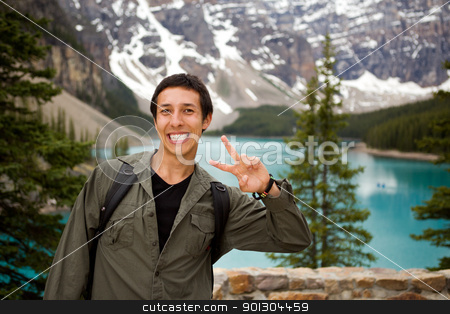 Happy Tourist stock photo, A portrait of a happy tourist in front of a scenic landscape by Tyler Olson
