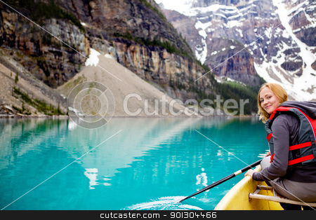 Woman Canoeing Portrait stock photo, A woman canoeing on Moraine Lake, a tight crop with copy space by Tyler Olson