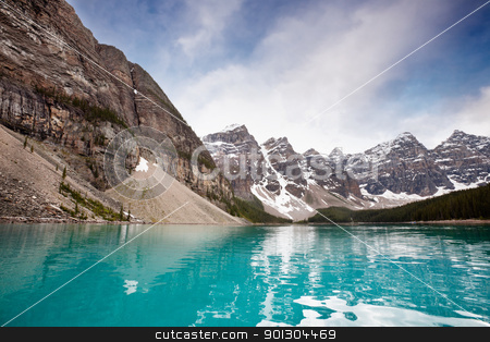 Calm water and mountain range stock photo, Scenic shot of calm blue water and mountain range against sky by Tyler Olson