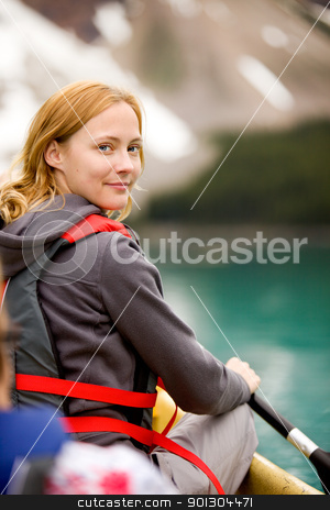 Woman in Canoe stock photo, A portrait of a smiling woman in a canoe on a glacial lake. by Tyler Olson