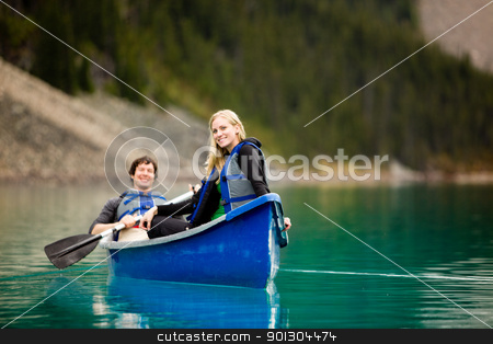 Couple Canoeing and Relaxing stock photo, A portrait of a happy woman on a canoeing trip with a man by Tyler Olson