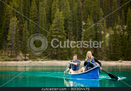 Couple Portrait in Canoe stock photo, A portrait of a happy copule in a canoe on a glacial lake by Tyler Olson