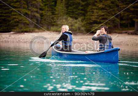 Canoe Adventure in Lake stock photo, A man and woman paddling in a canoe on a lake by Tyler Olson
