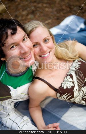 Happy Couple Picnic stock photo, A portrait of a smiling happy couple outdoors on a picnic blanket by Tyler Olson