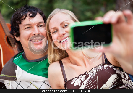 Young cheerful couple photographing themselves stock photo, Happy young couple taking photo of themselves by Tyler Olson