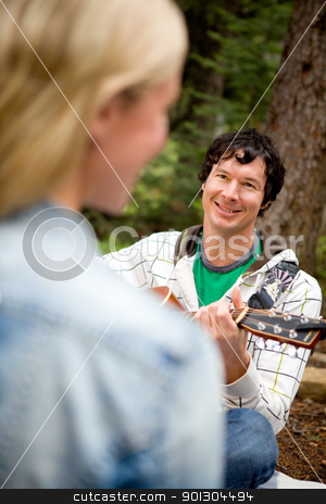 Man Serenading a Woman with Guitar stock photo, A man and woman in a forest with a guitar by Tyler Olson