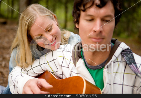 Outdoor Guitar Couple stock photo, A couple enjoying themselves outdoors with a guitar, focus on woman by Tyler Olson