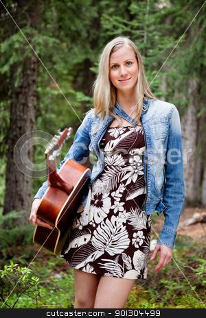 Female holding guitar against trees stock photo, Attractive young female holding guitar against trees by Tyler Olson