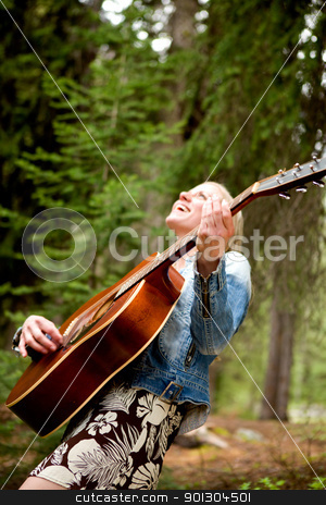 Woman Singing Free in the Forest stock photo, A woman singing freely in the forest with a guitar - sharp focus on guitar  by Tyler Olson