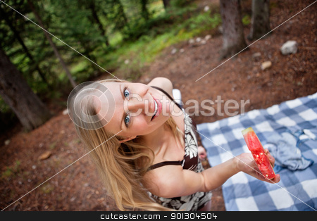 Blond woman eating watermelon while picnic stock photo, Top view of beautiful blond woman eating watermelon on picnic by Tyler Olson
