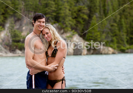 Couple Portrait on Beach stock photo, A portrait of a happy near a river in Banff, Canada by Tyler Olson