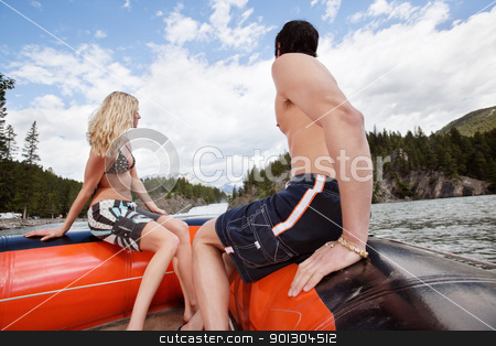Young couple in raft looking at view stock photo, Young couple in raft looking at view under cloudy sky by Tyler Olson