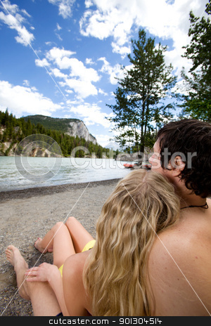 Couple Relax Banff stock photo, A couple relaxing near a river in Banff, Canada by Tyler Olson